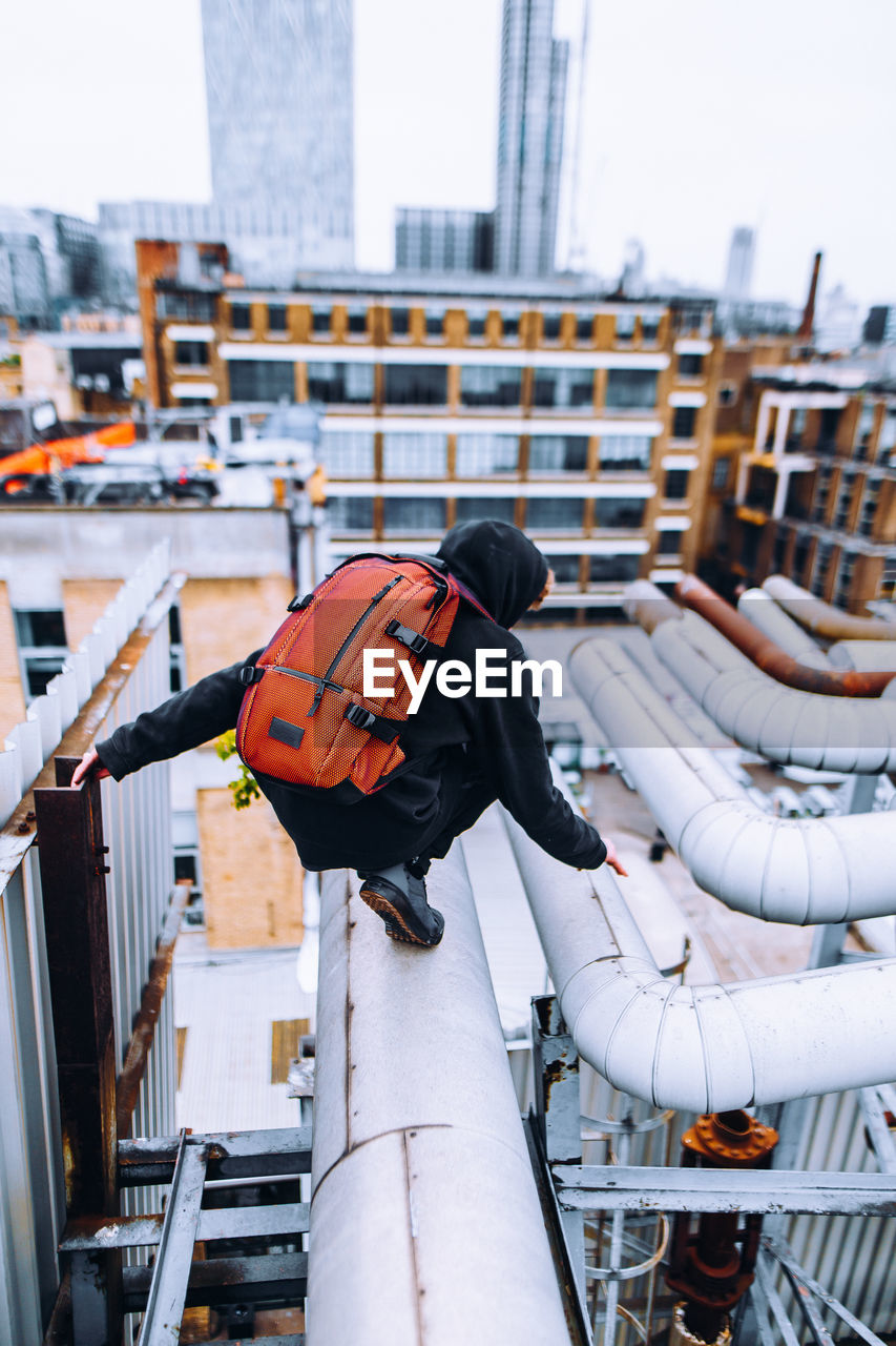 Side View Of Man With Backpack Crouching On Pipe