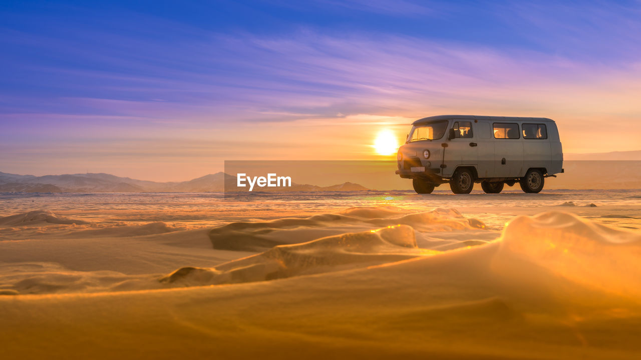 sunset, sky, mode of transportation, scenics - nature, transportation, land vehicle, beauty in nature, nature, environment, desert, land, non-urban scene, landscape, travel, outdoors, no people, cold temperature, winter, cloud - sky, arid climate, climate