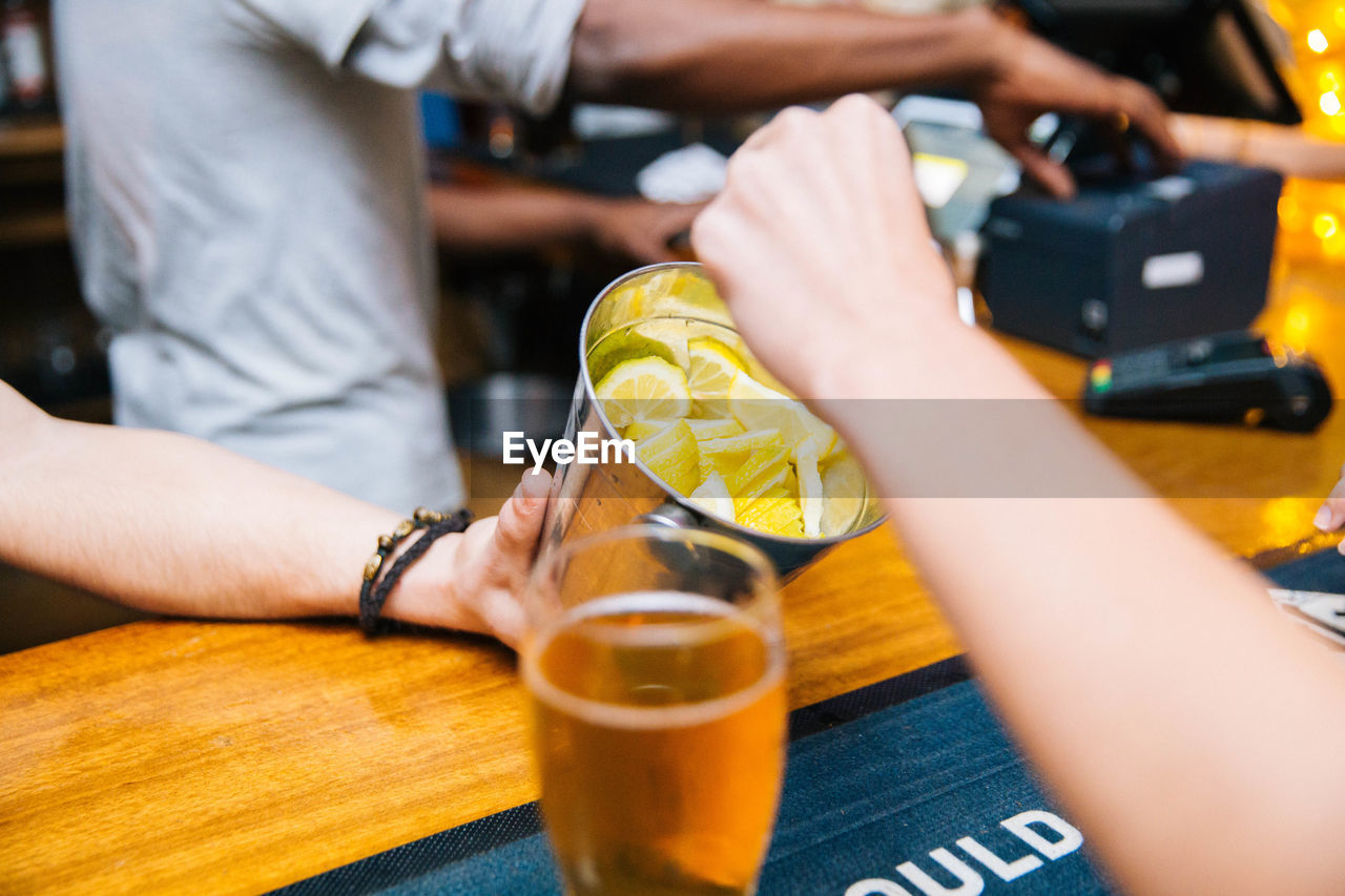 human hand, real people, hand, human body part, table, food and drink, indoors, holding, people, midsection, lifestyles, drink, men, refreshment, close-up, leisure activity, selective focus, glass, technology, finger