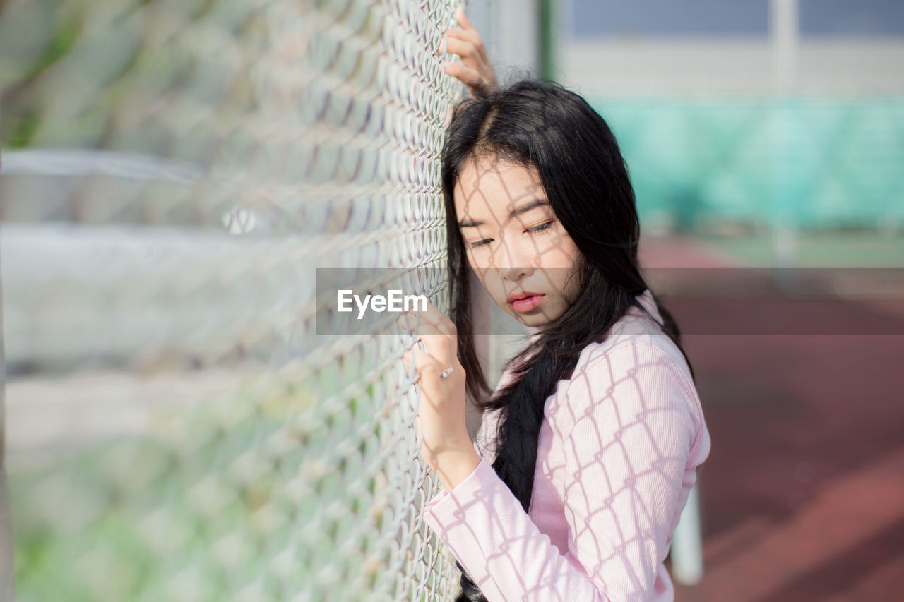 Side View Of Thoughtful Young Woman Looking Away By Net At Court