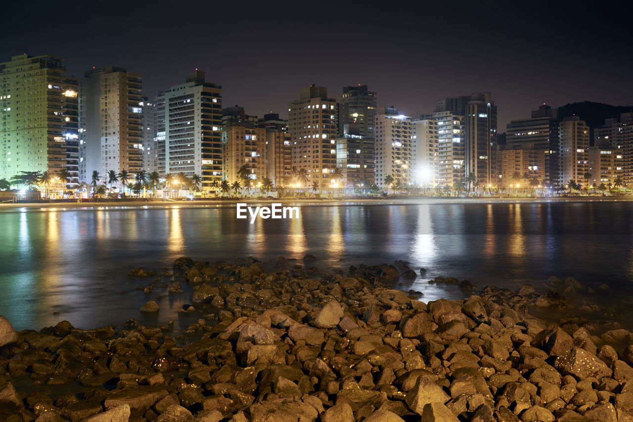 building exterior, water, architecture, built structure, night, illuminated, city, sky, nature, rock, building, river, no people, reflection, solid, beach, rock - object, outdoors, office building exterior, cityscape, skyscraper