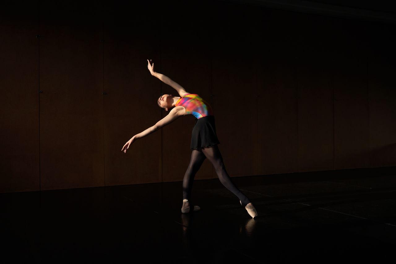 FULL LENGTH OF WOMAN DANCING AT CONCERT