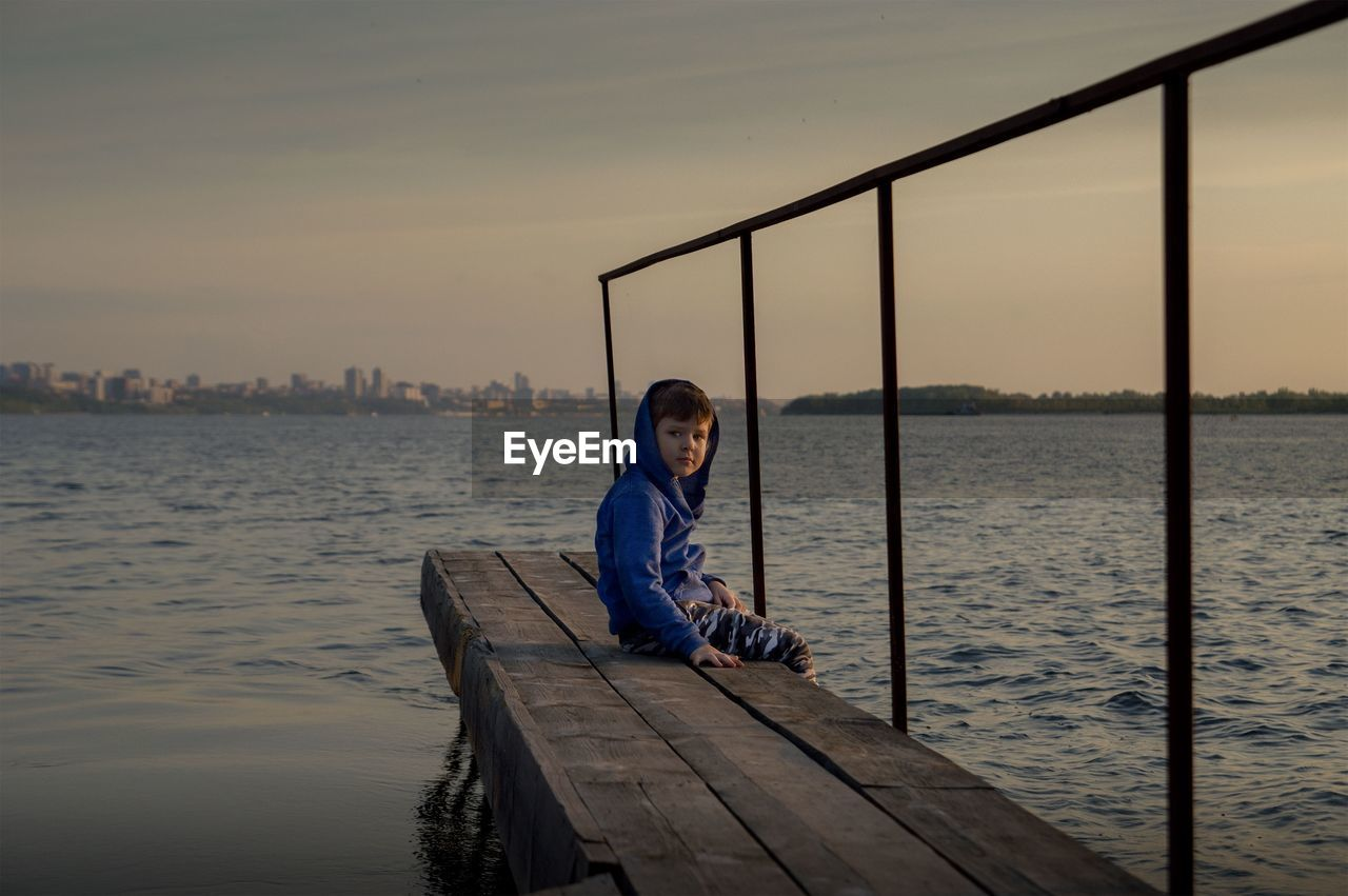 Portrait of boy sitting by lake on jetty during sunset