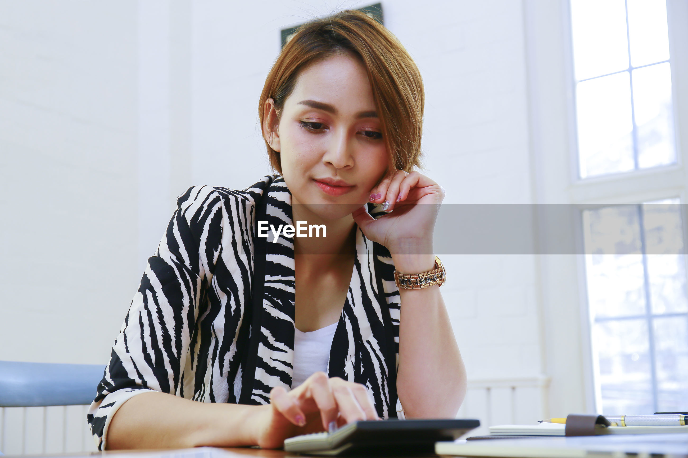 Beautiful businesswoman using calculator at desk in office