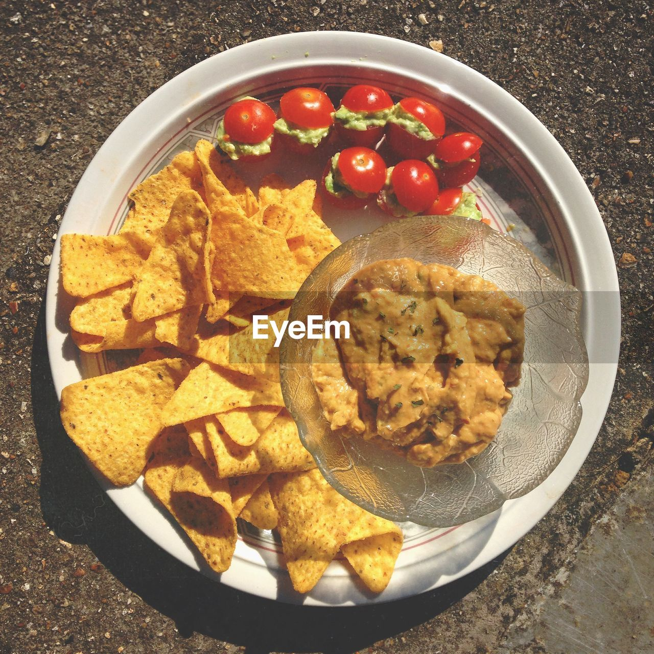 Nachos With Sauce And Tomato In Plate On Table