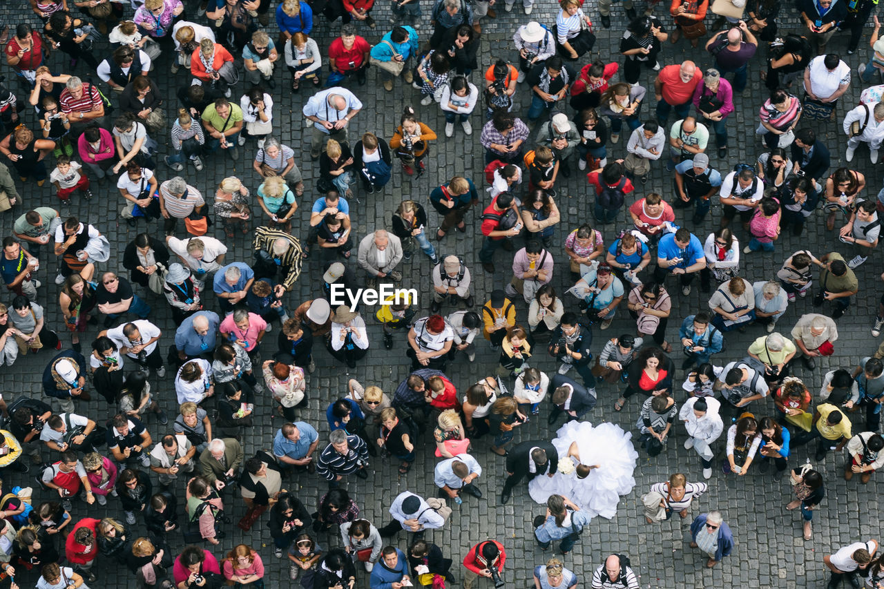 High Angle View Of Married Couple Standing In Crowd On Footpath
