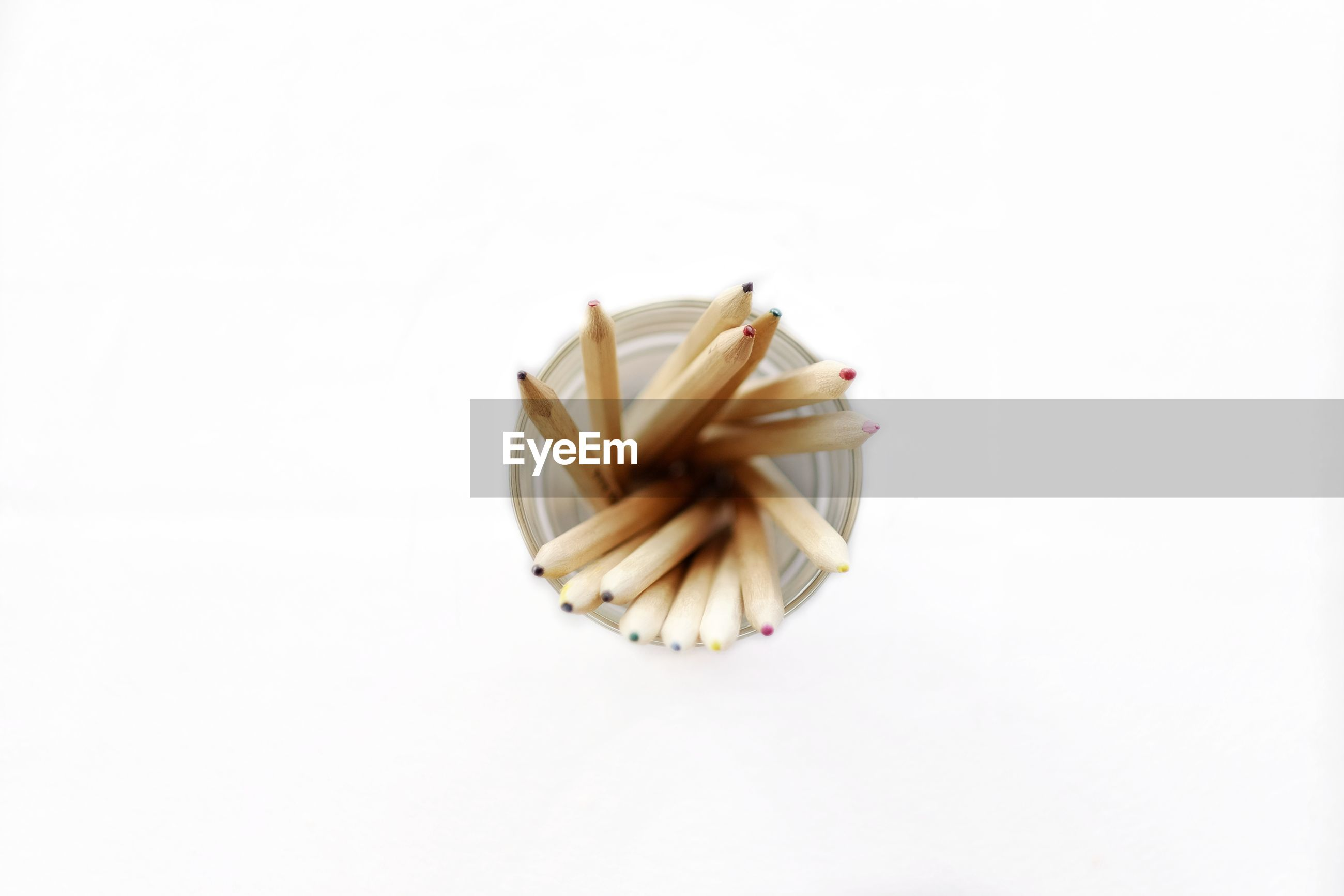 Directly above shot of pencils in container on white background