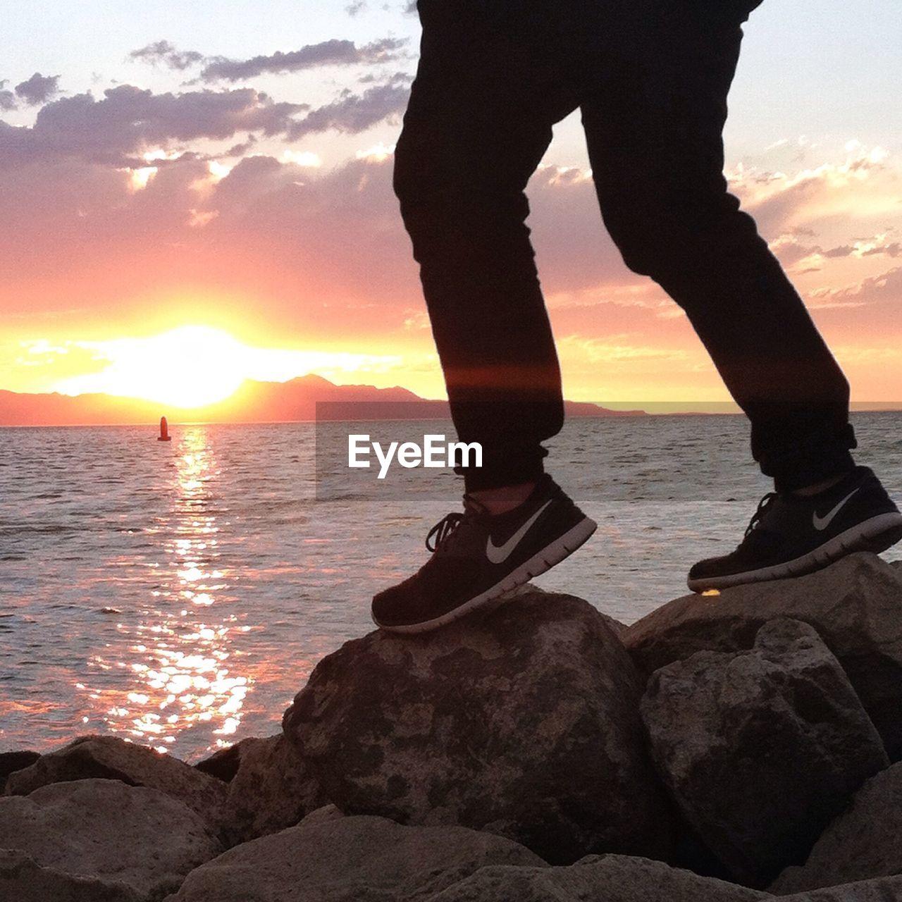 Man standing on rocky coastline