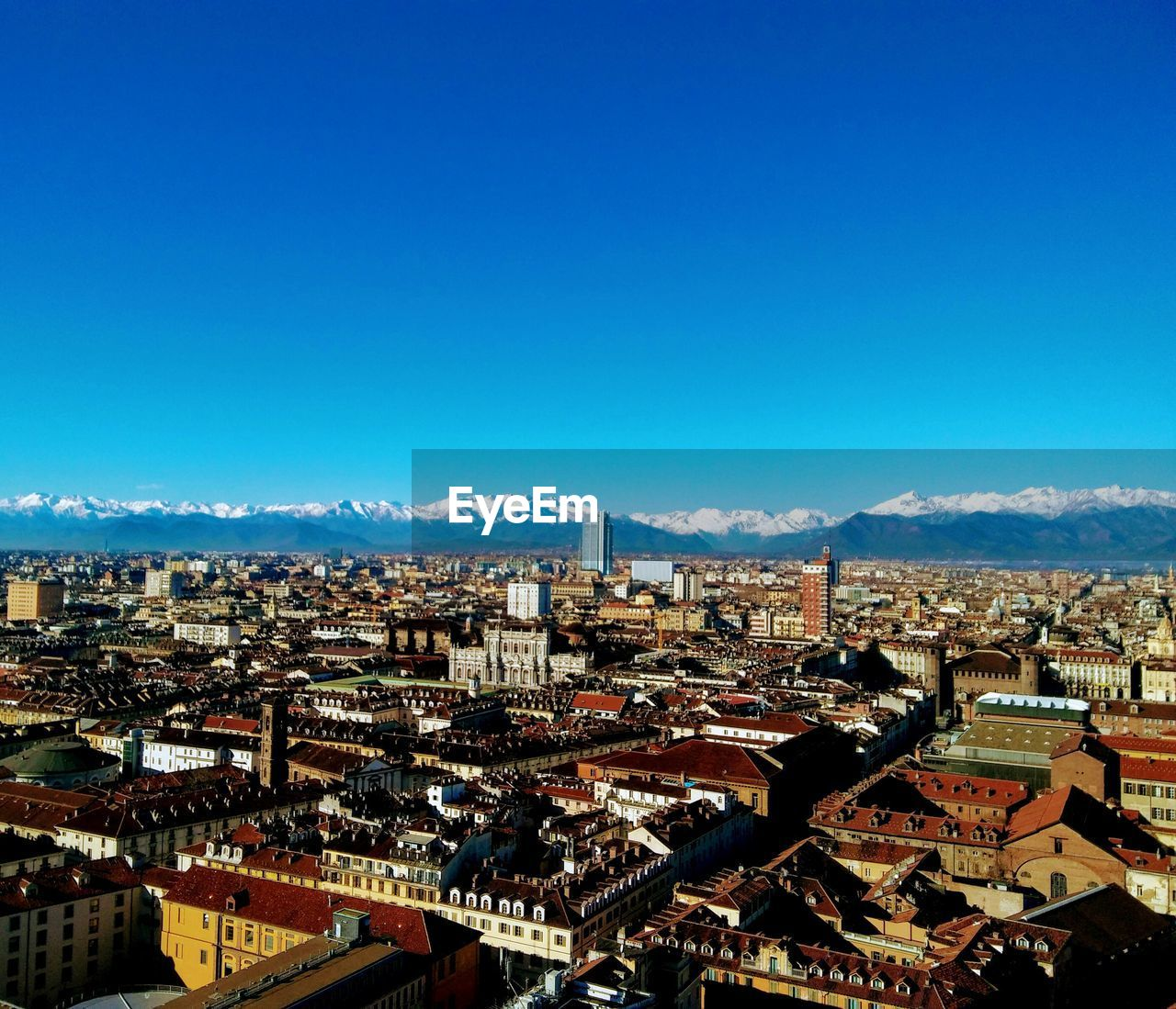 architecture, building exterior, cityscape, built structure, crowded, residential district, mountain, high angle view, residential building, city, day, copy space, blue, outdoors, mountain range, sky, town, roof, community, clear sky, beauty in nature, nature