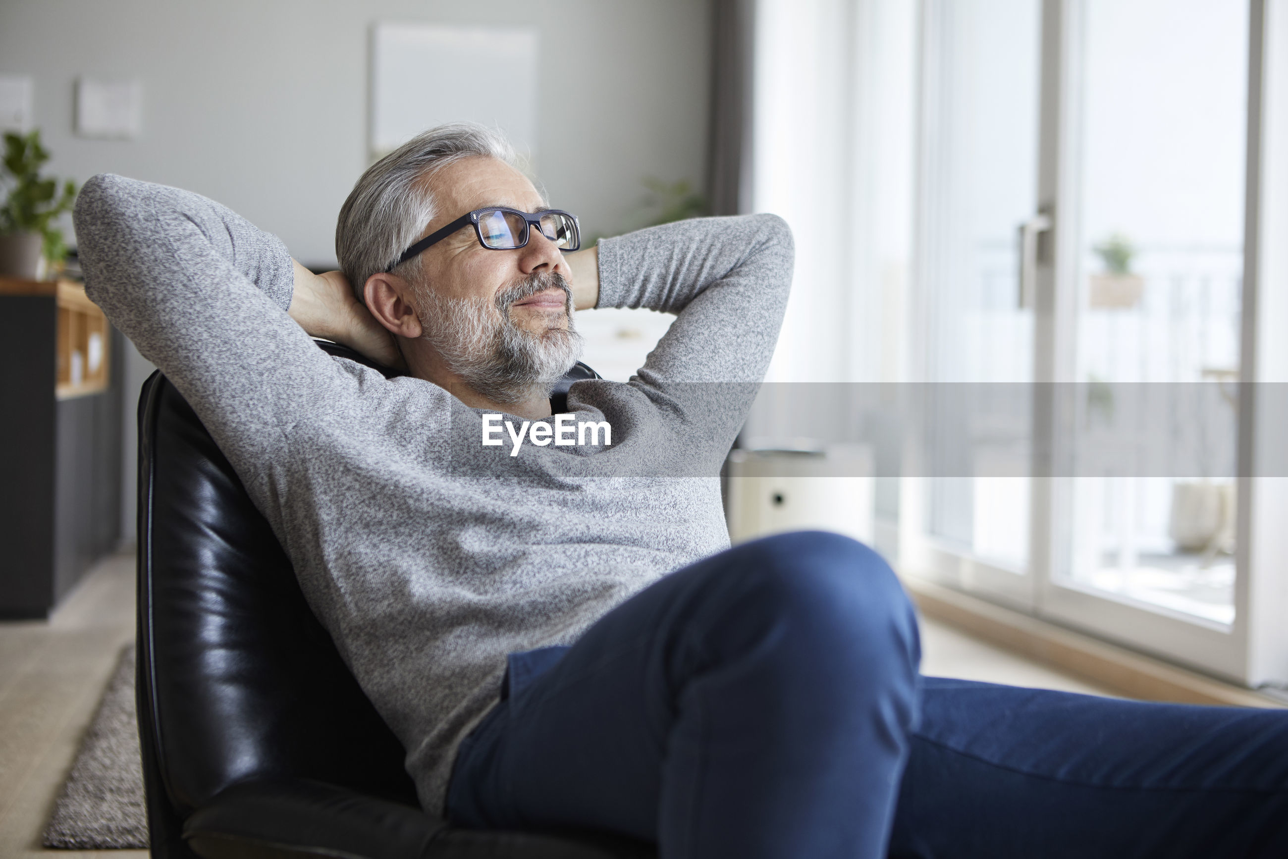 MIDSECTION OF MAN SITTING ON SOFA
