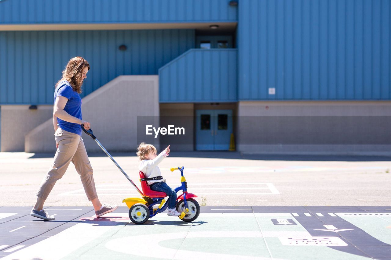 Side View Of Woman Pushing Her Daughter Sitting On Tricycle During Sunny Day