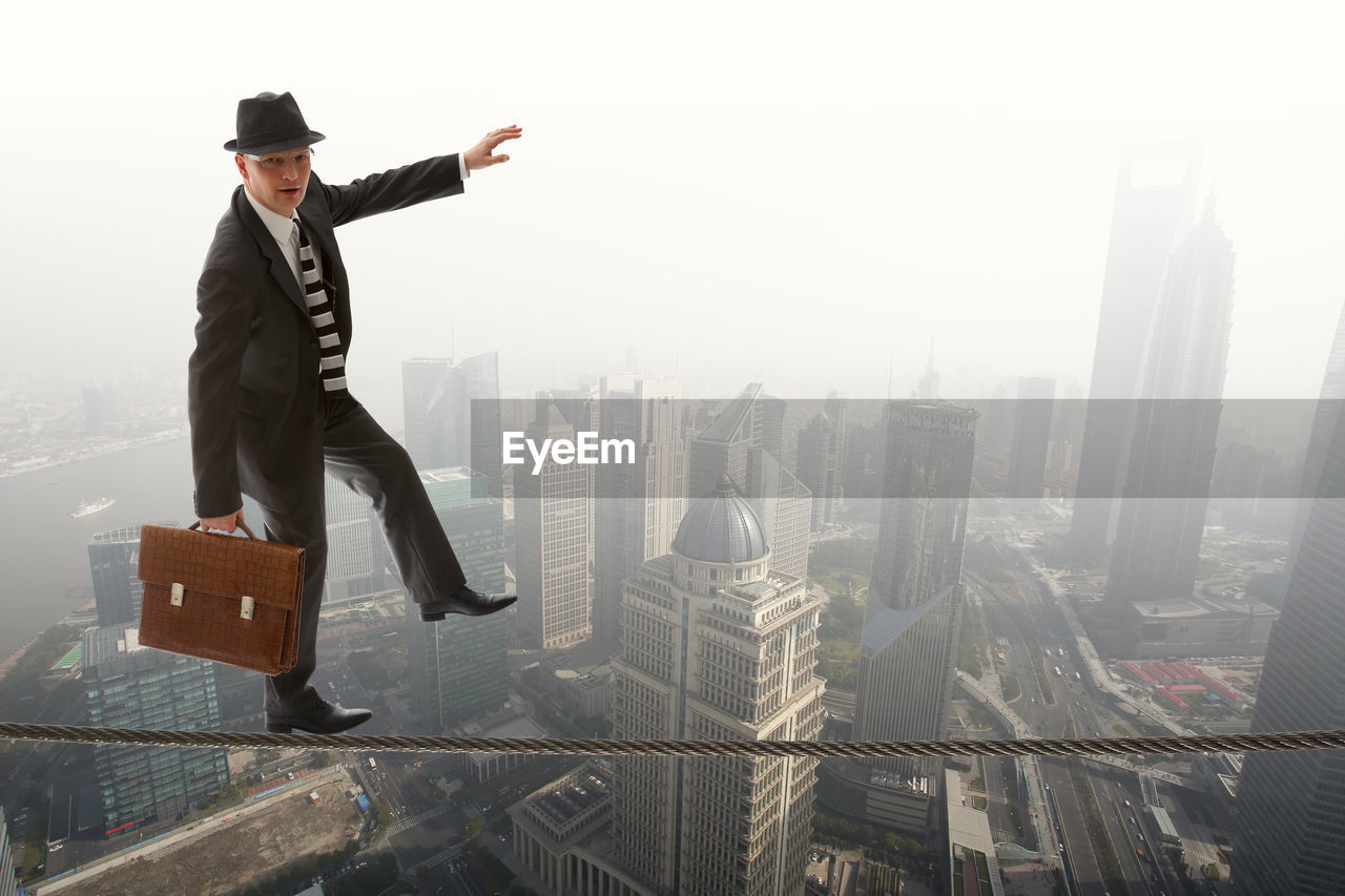 Digital Composite Image Of Businessman Holding Briefcase On Tightrope Over Cityscape