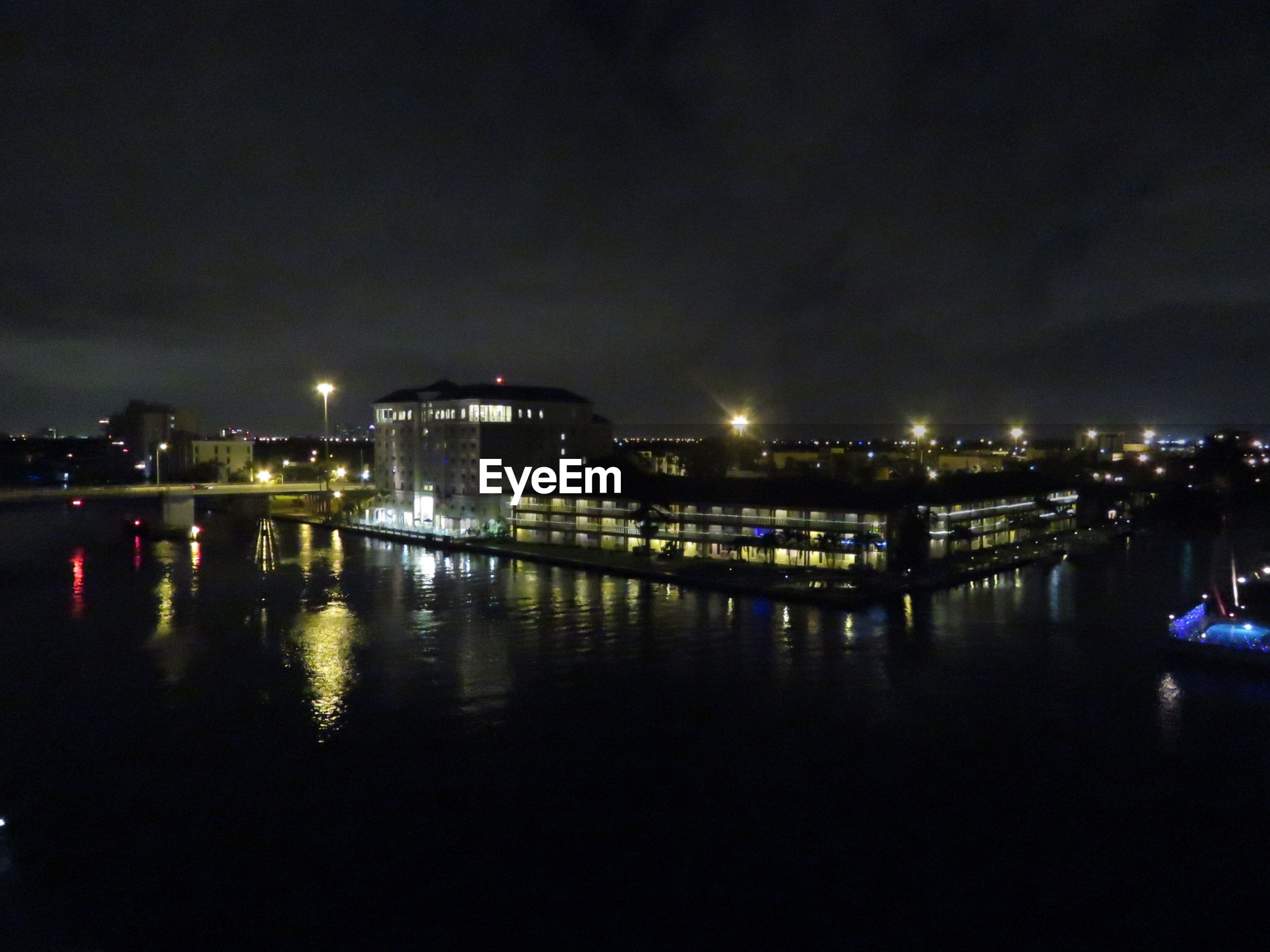 ILLUMINATED CITYSCAPE BY RIVER AGAINST SKY