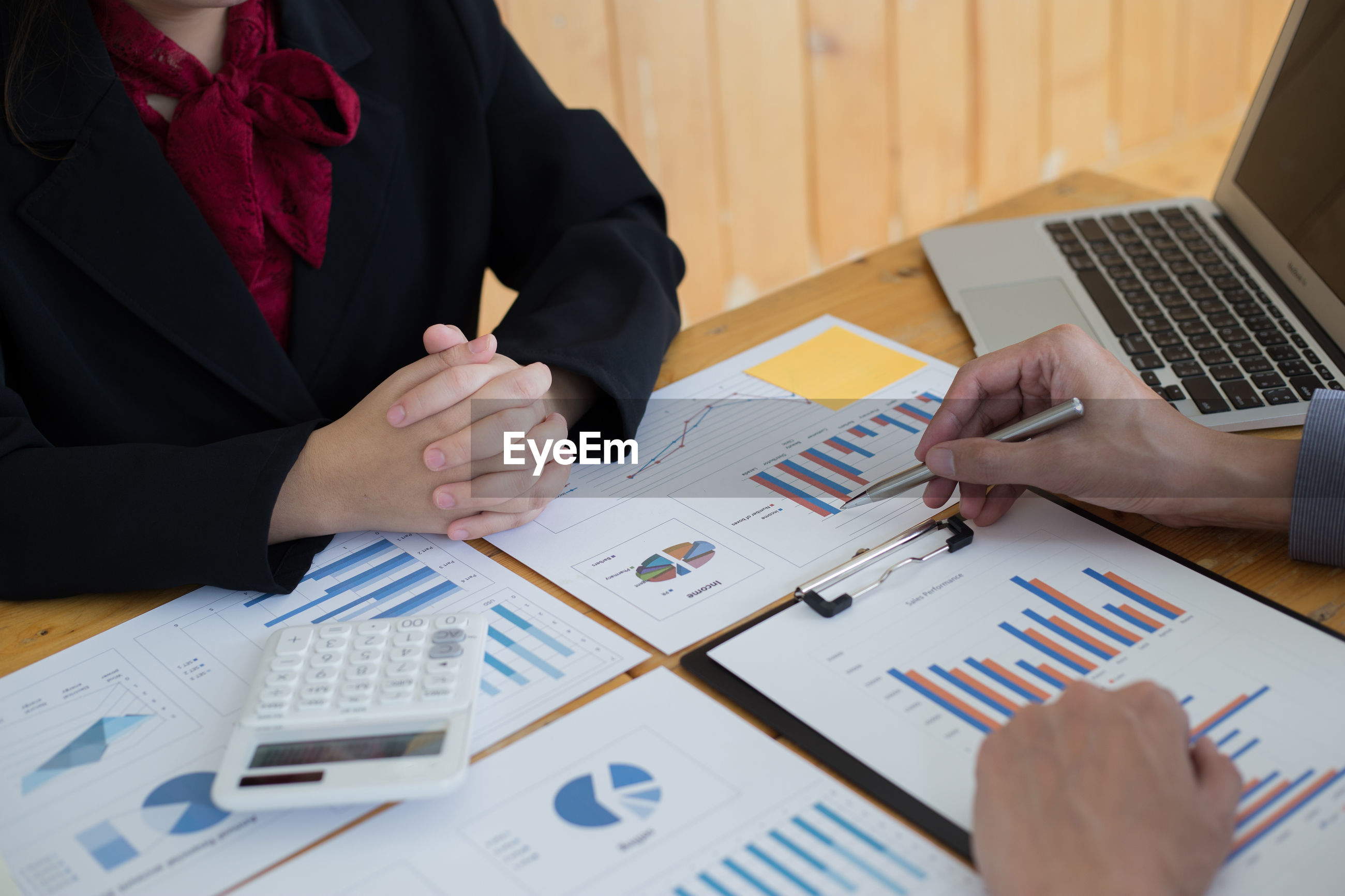 Cropped image of business colleagues analyzing graph on desk in office