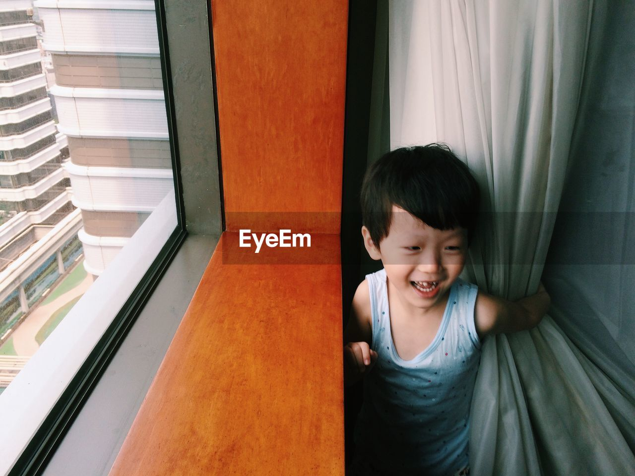 Cute playful boy standing by window at home