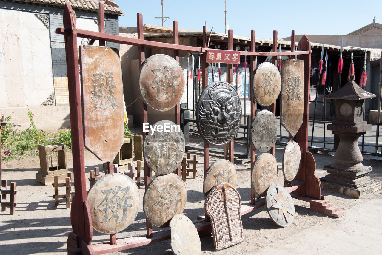 day, sunlight, nature, architecture, art and craft, no people, large group of objects, outdoors, built structure, building exterior, hanging, creativity, variation, craft, antique, choice, old, wood - material, music