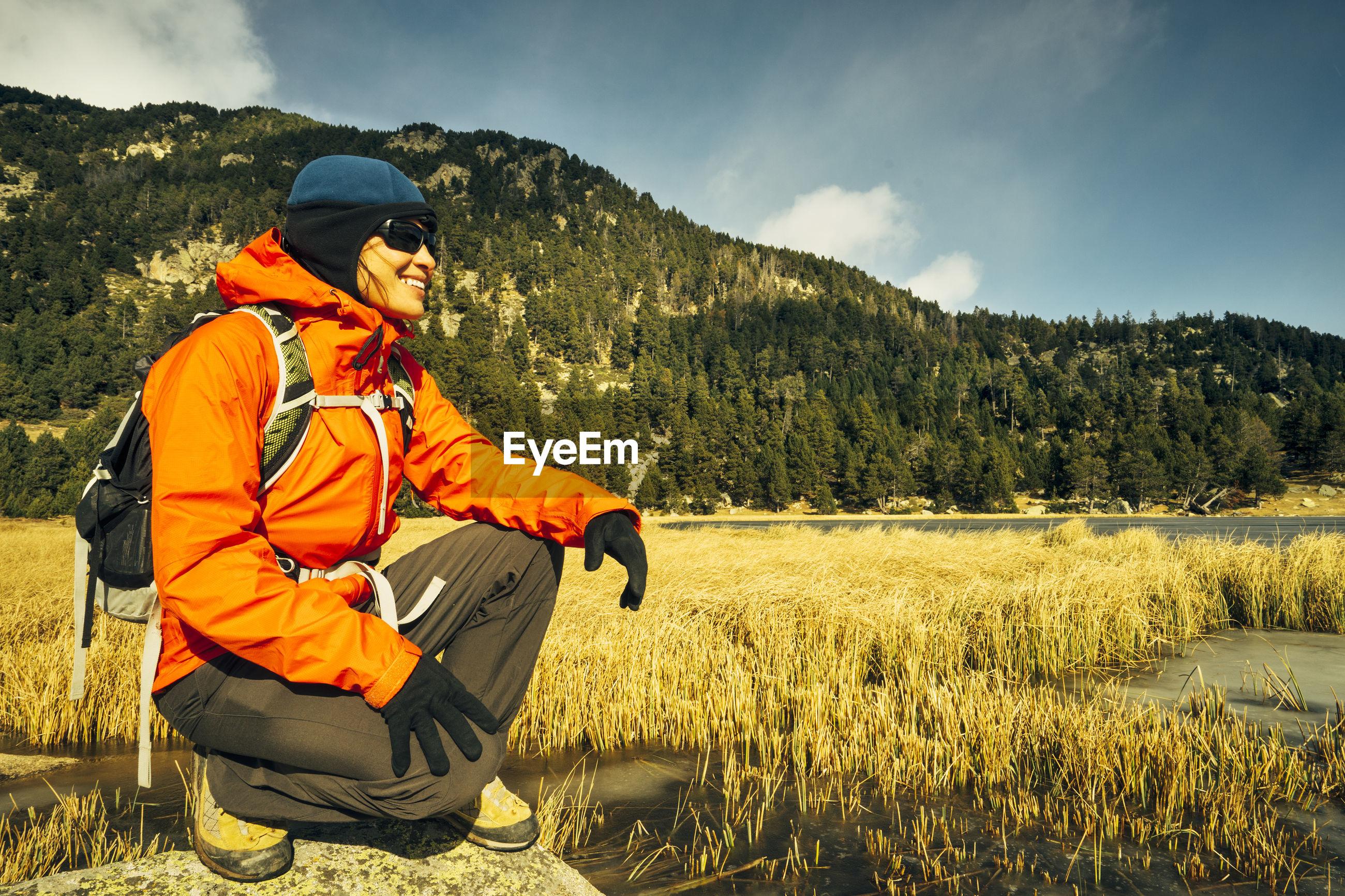 Happy hiker crouching on rock against sky