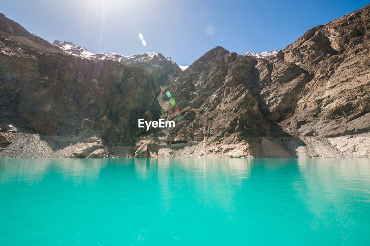 water, mountain, beauty in nature, sky, nature, tranquil scene, tranquility, waterfront, scenics - nature, rock, no people, day, sunlight, reflection, non-urban scene, environment, solid, rock - object, idyllic, outdoors, swimming pool, formation, turquoise colored