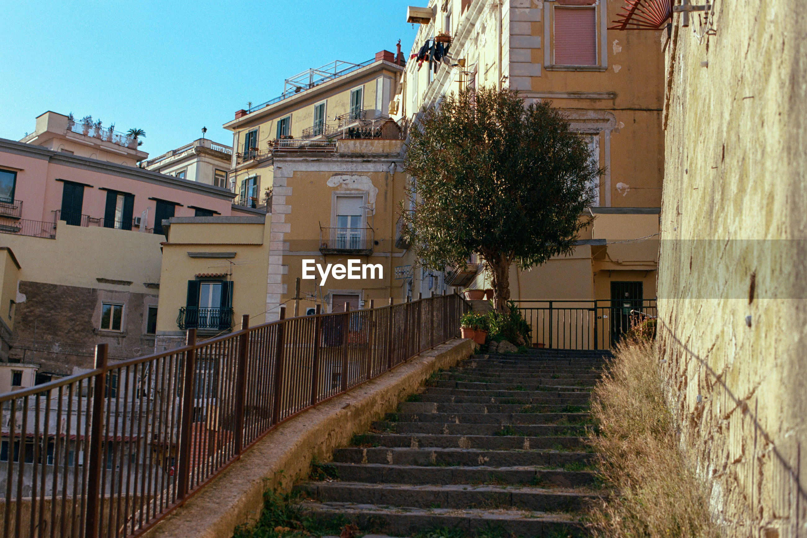 LOW ANGLE VIEW OF STAIRCASE AGAINST BUILDINGS