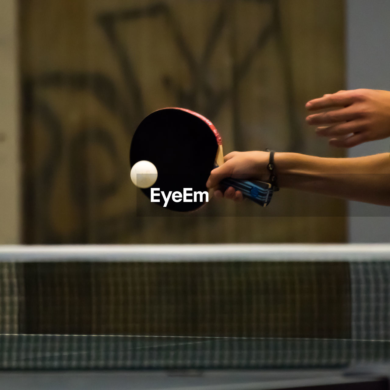 Cropped hand playing table tennis in court