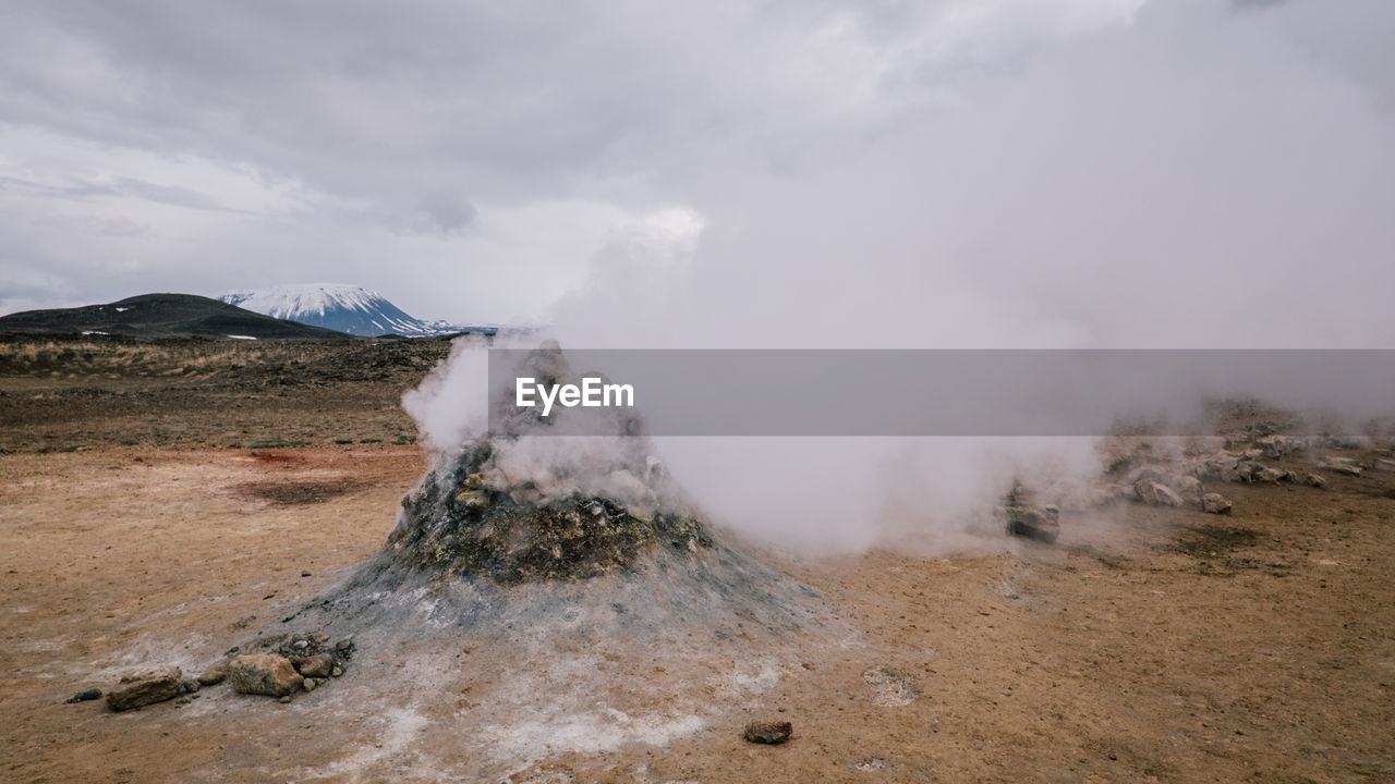 Steam Emitting From Volcano Against Cloudy Sky