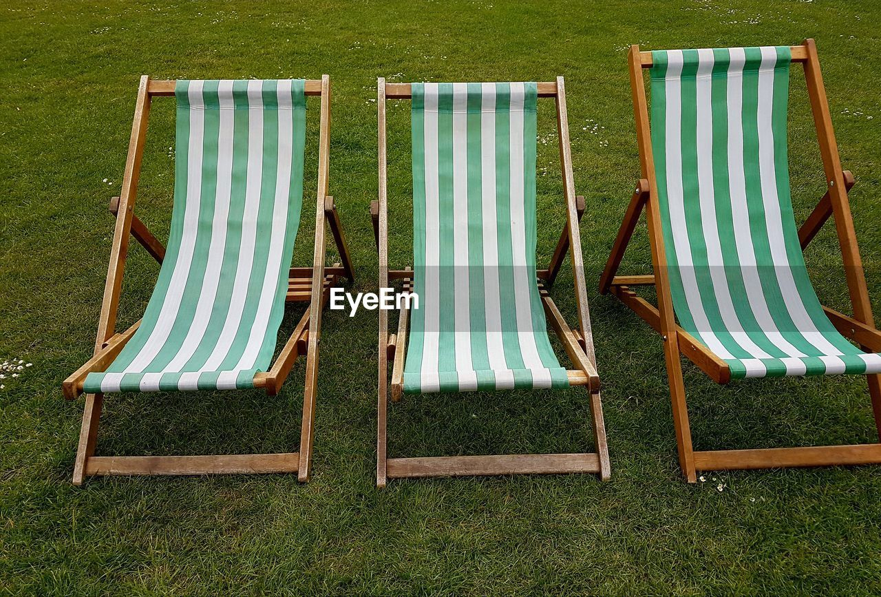 grass, absence, plant, nature, striped, deck chair, day, no people, relaxation, chair, land, empty, green color, seat, in a row, side by side, outdoors, field, group of objects, blue, foldable, outdoor chair