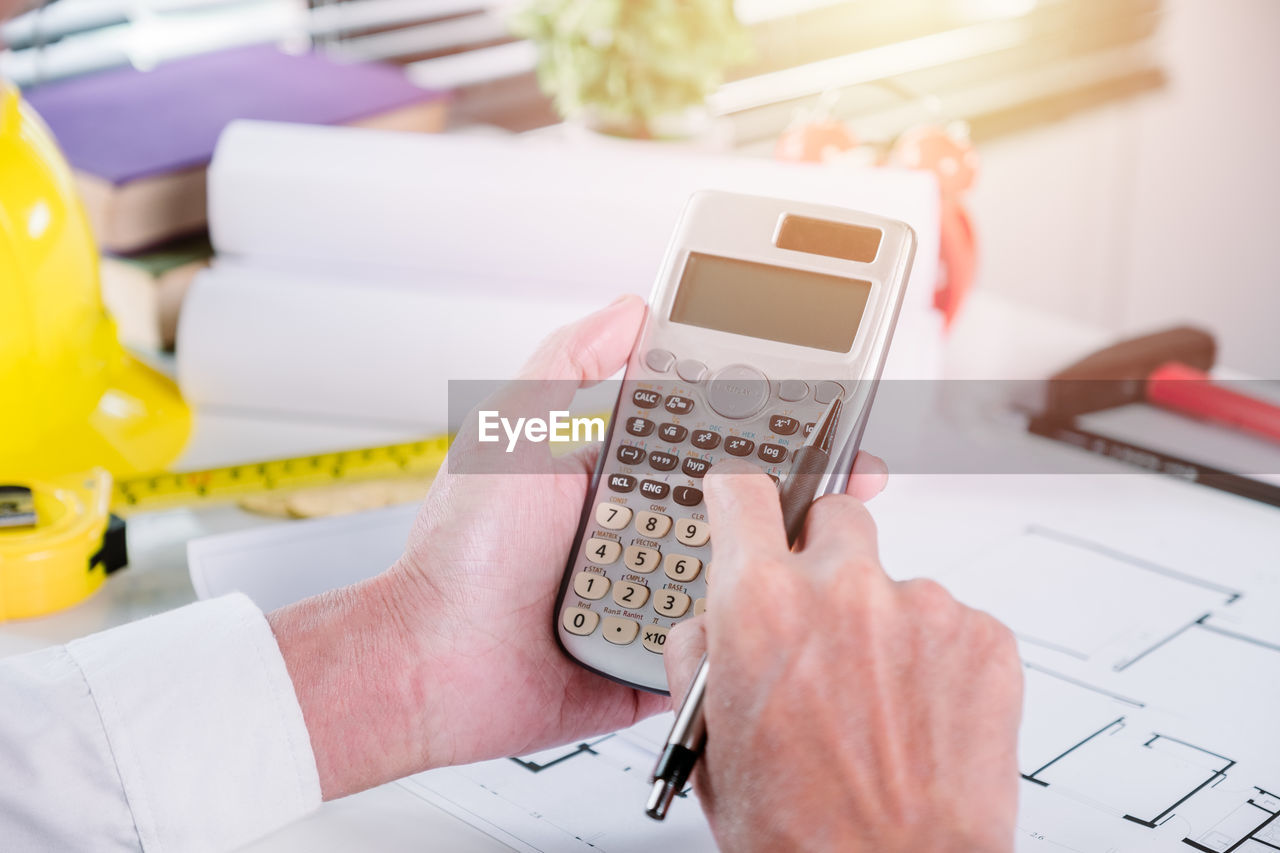 human hand, wireless technology, technology, hand, holding, indoors, connection, one person, portable information device, communication, real people, table, smart phone, mobile phone, telephone, human body part, close-up, high angle view, focus on foreground, calculating