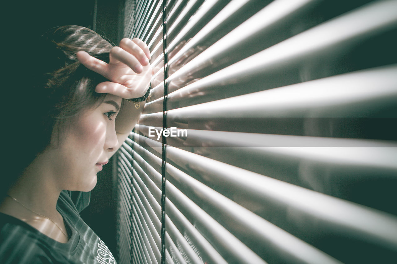 Side View Of Thoughtful Woman Looking Through Window Blinds