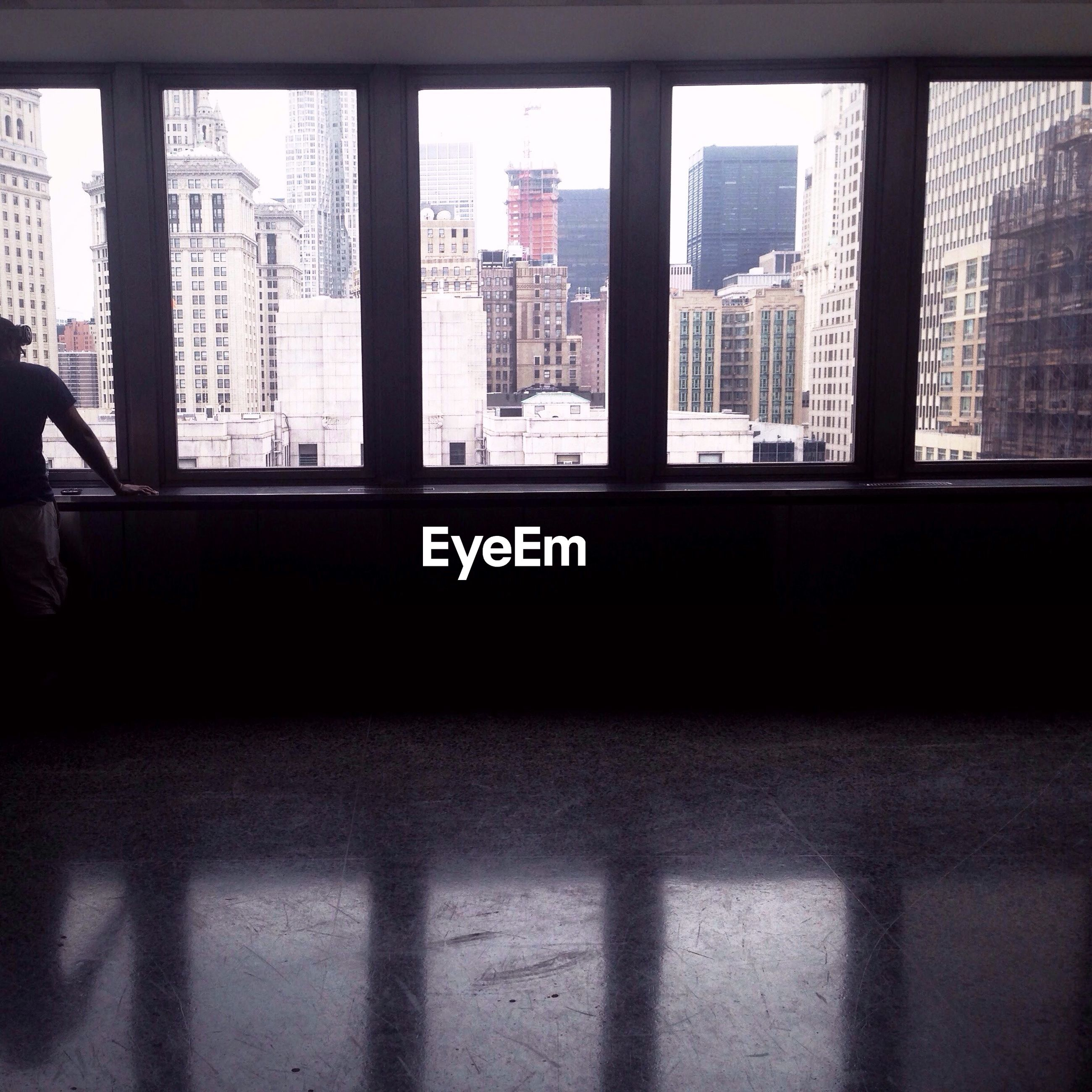Person standing in empty room by window