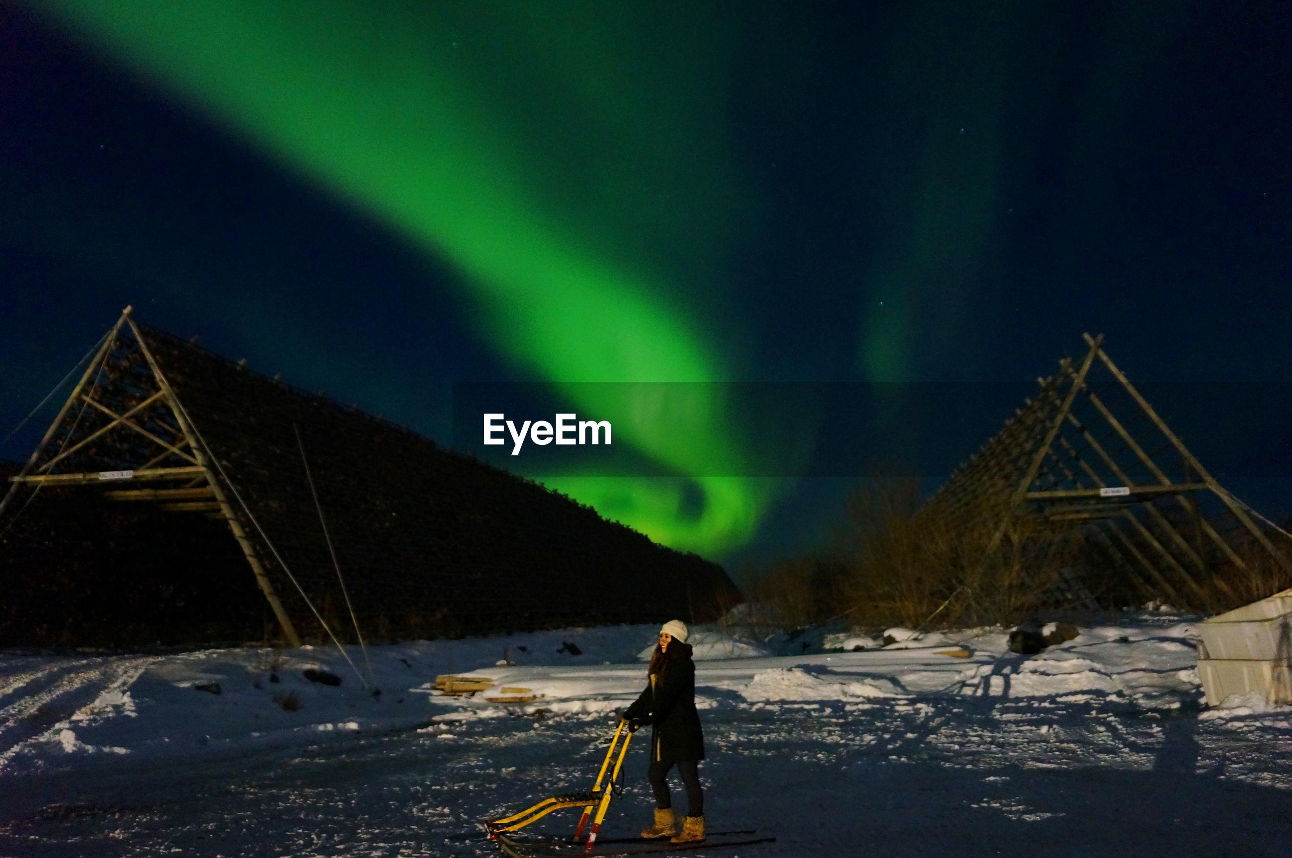 Woman standing on snow covered mountain against aurora polaris