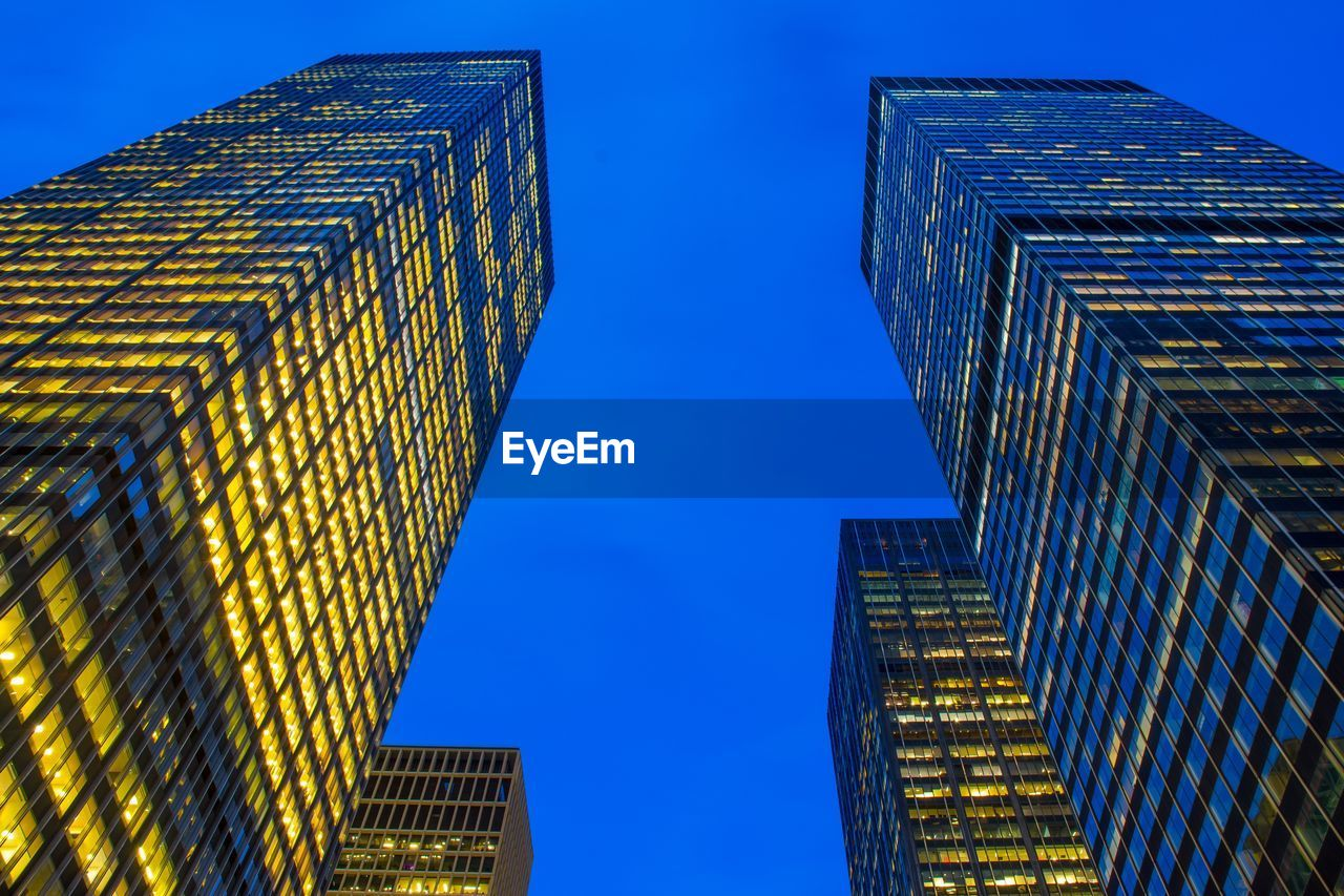 low angle view, building exterior, architecture, built structure, building, modern, city, sky, office building exterior, tall - high, no people, blue, office, clear sky, skyscraper, glass - material, nature, tower, dusk, illuminated, financial district