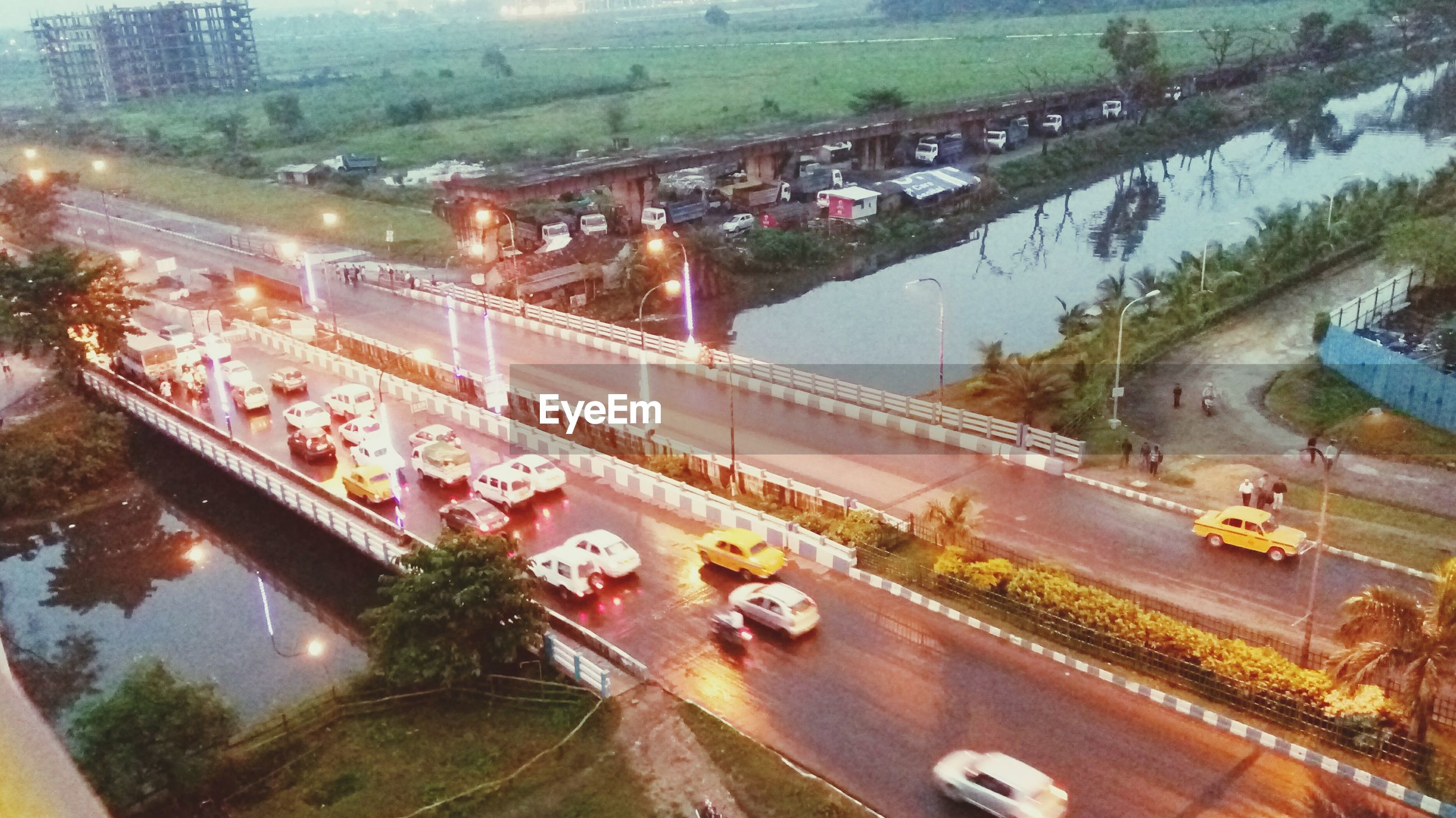 transportation, high angle view, car, land vehicle, tree, architecture, road, built structure, mode of transport, illuminated, outdoors, bridge - man made structure, no people, city, water, day