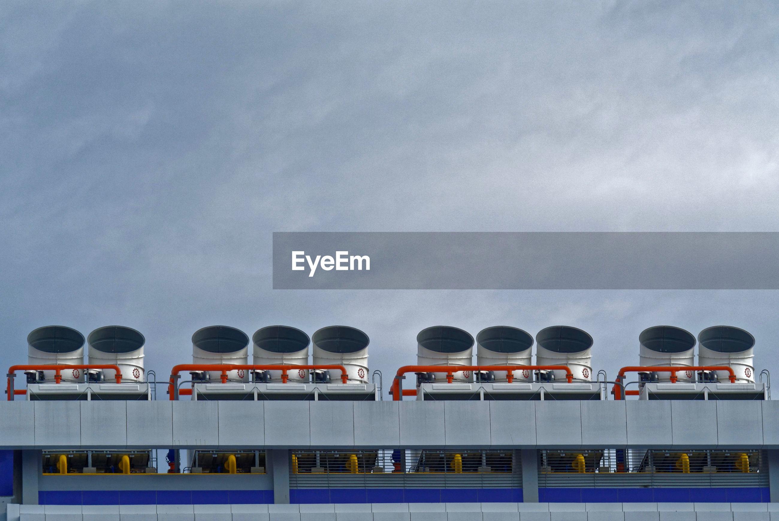 Low angle view of ship smoke stacks against sky