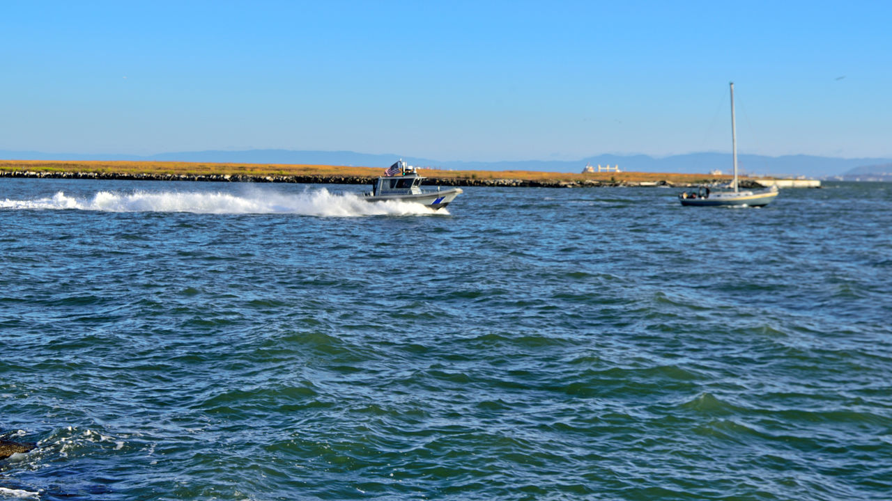 water, nautical vessel, transportation, sky, motion, sea, waterfront, mode of transportation, clear sky, beauty in nature, day, nature, speed, scenics - nature, speedboat, copy space, wave pattern, blue, wake - water, outdoors, no people, sailboat