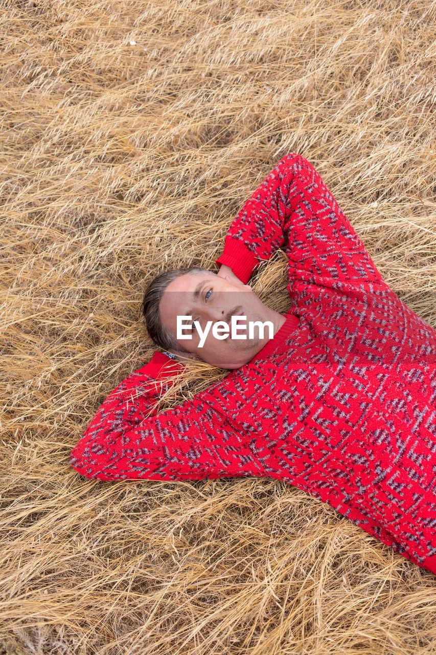 High angle portrait of man lying on grass
