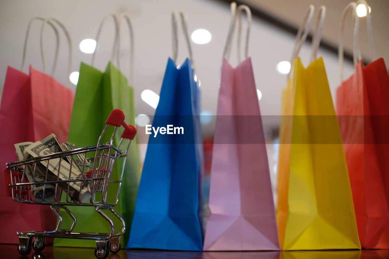 Close-Up Of Colorful Shopping Bags With Paper Currencies In Miniature Shopping Cart On Wooden Table