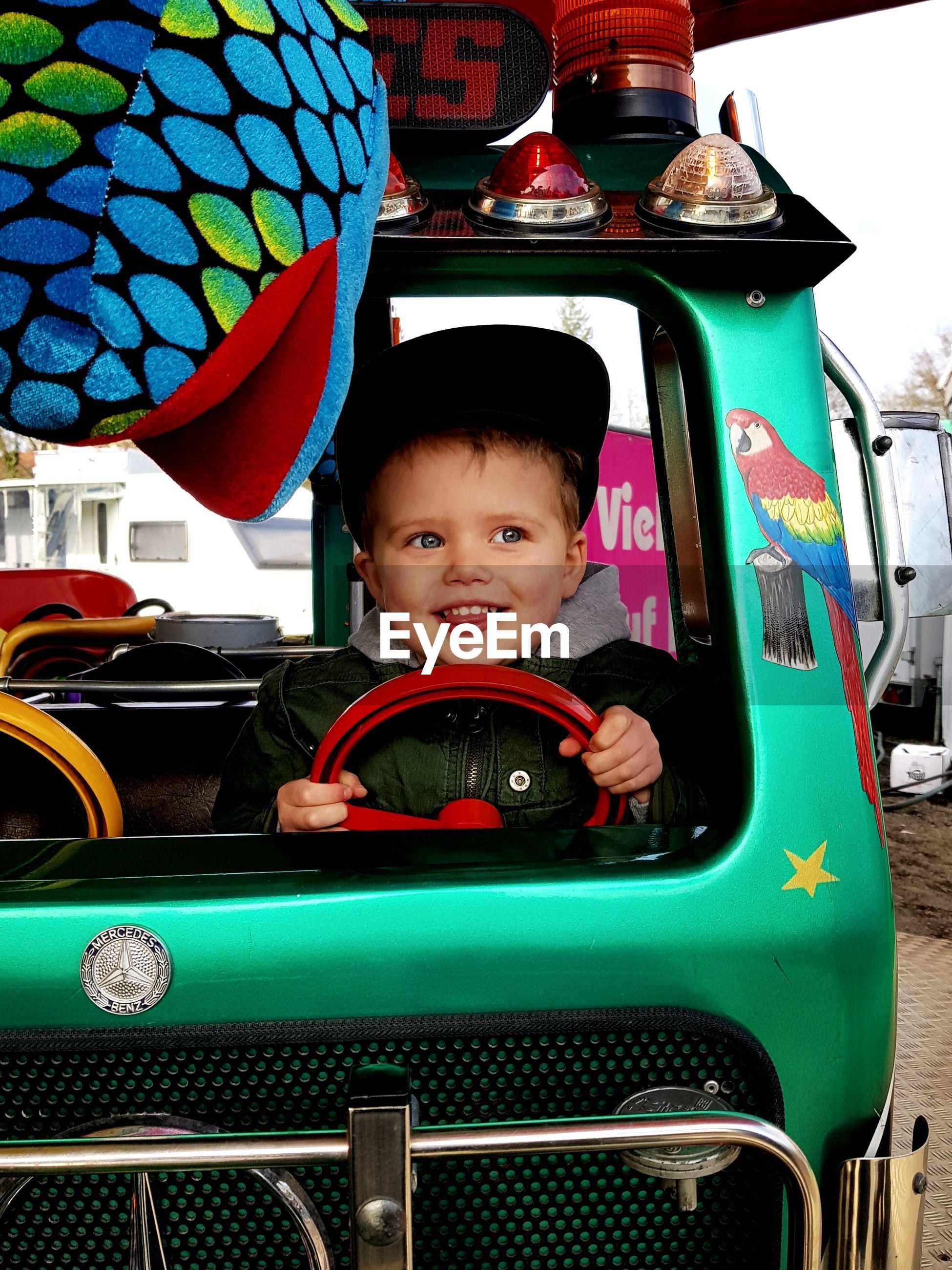 Cheerful boy riding toy car on footpath