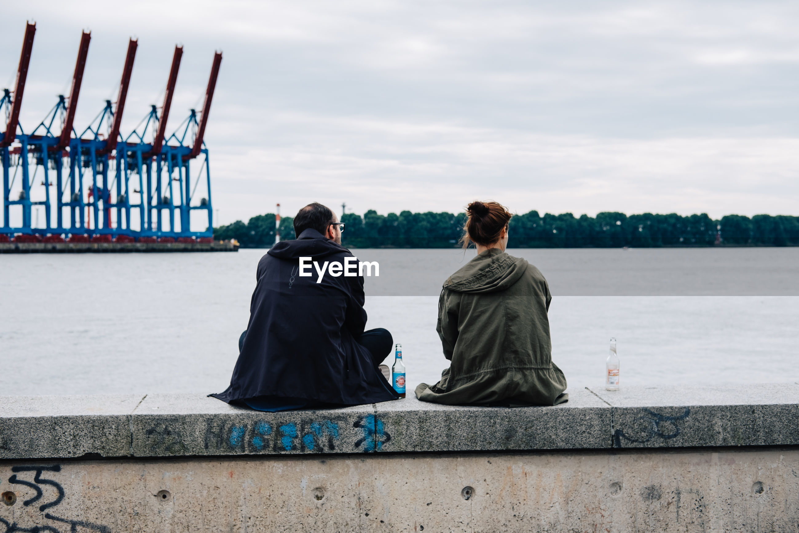 Rear view of couple sitting on wall against harbor
