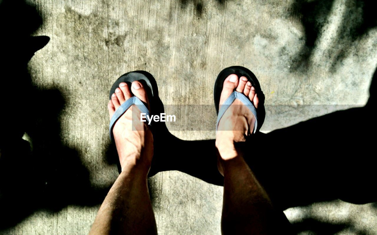 low section, human leg, one person, real people, human body part, standing, personal perspective, human foot, shoe, day, outdoors, high angle view, shadow, sunlight, leisure activity, lifestyles, men, one man only, human hand, nature, close-up, adult, people