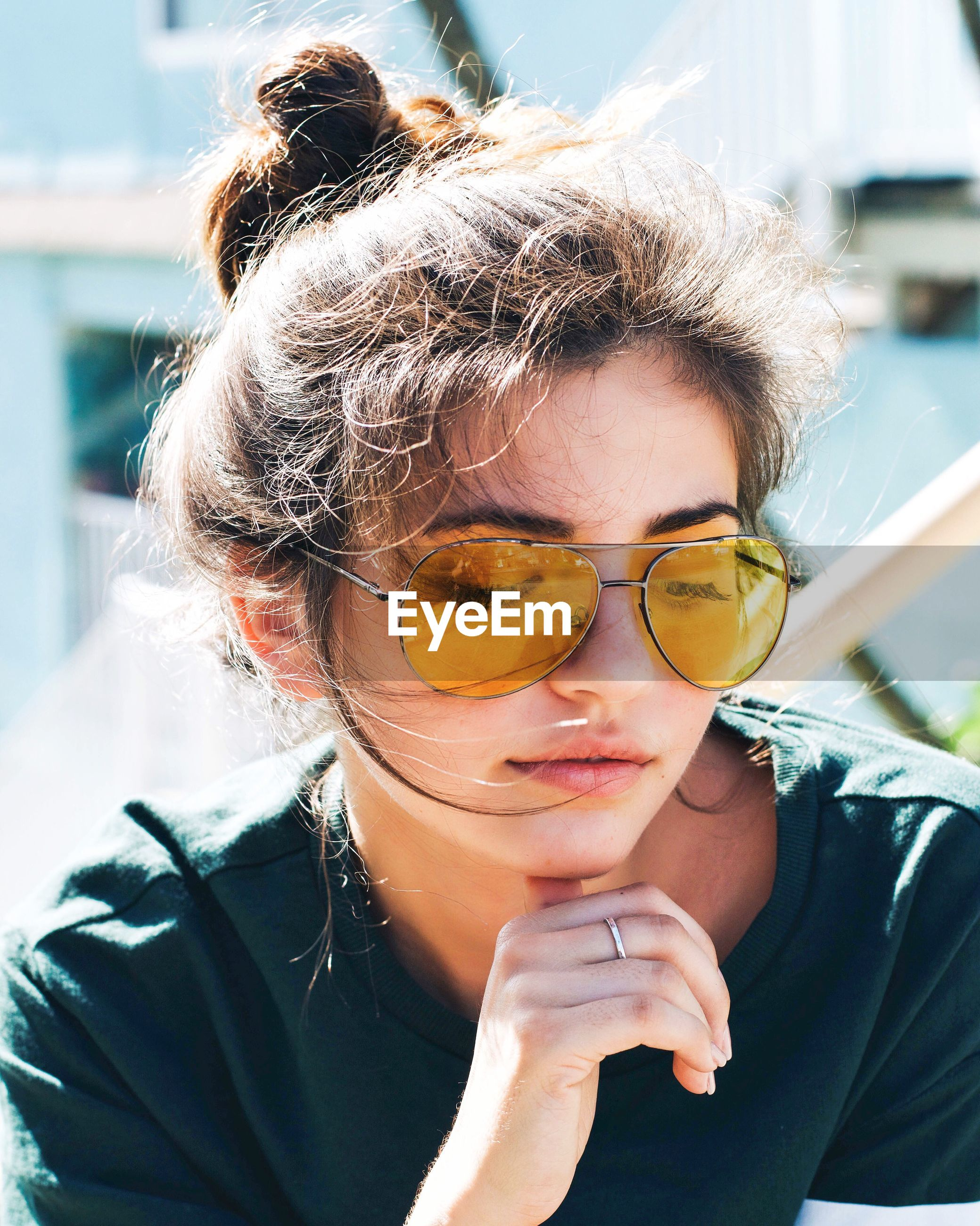 Close-up of young woman wearing yellow sunglasses outdoors