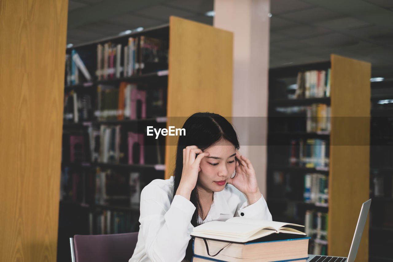 Young woman reading book while sitting in library