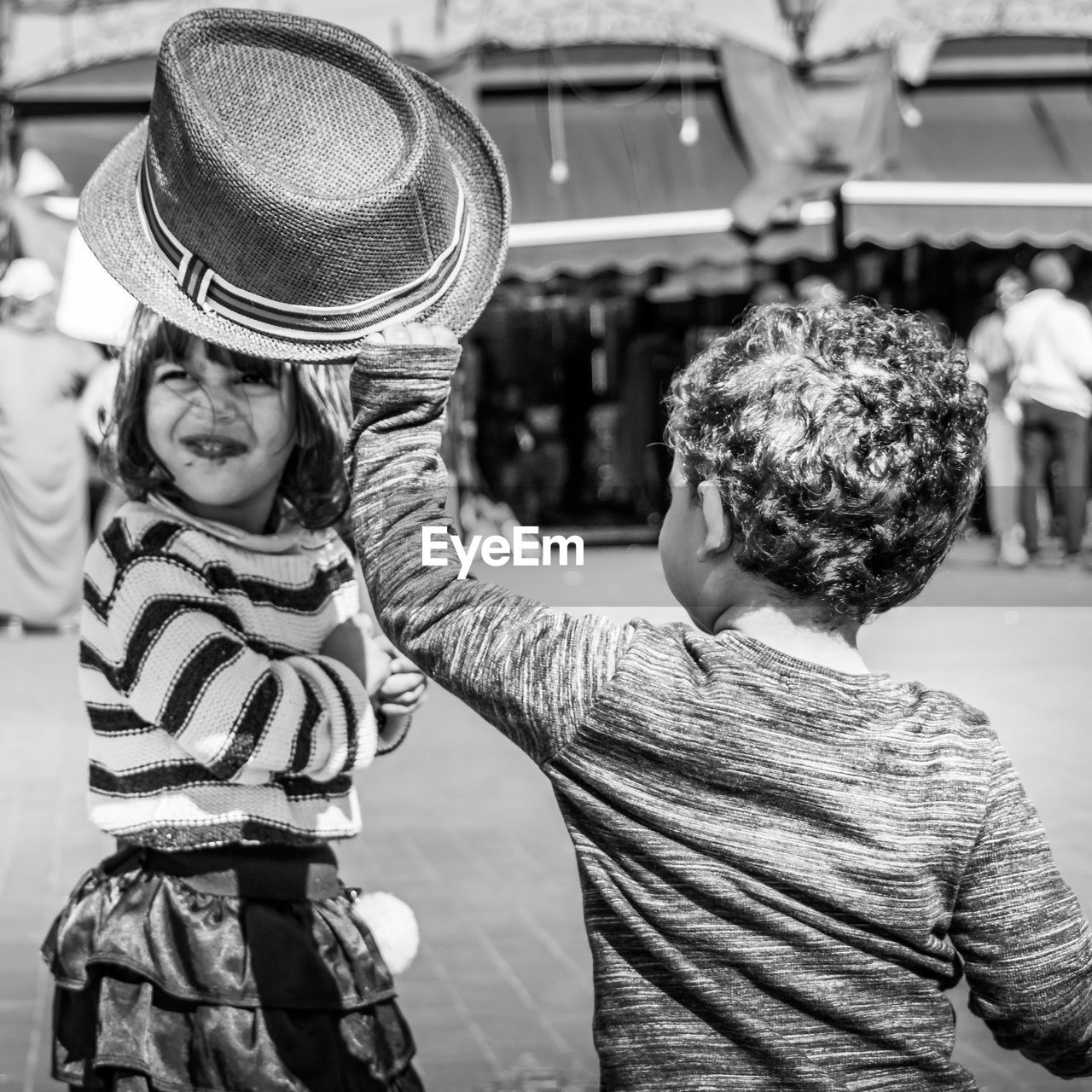 child, childhood, hat, two people, men, boys, males, clothing, real people, leisure activity, girls, females, bonding, casual clothing, togetherness, love, lifestyles, rear view, focus on foreground, innocence, positive emotion, sister