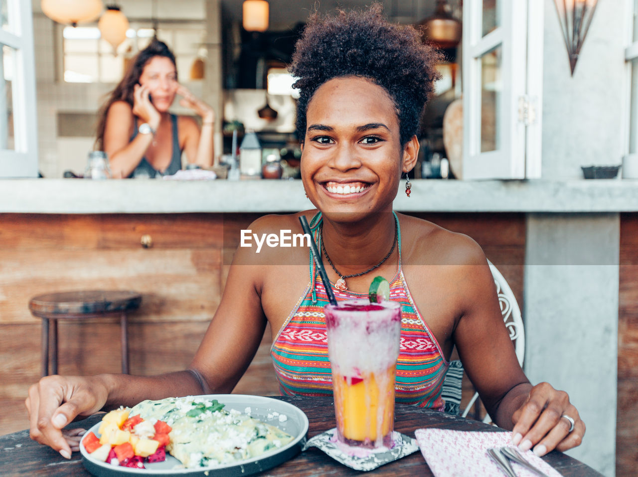 Portrait Of Smiling Young Woman Having Food And Drink In Restaurant