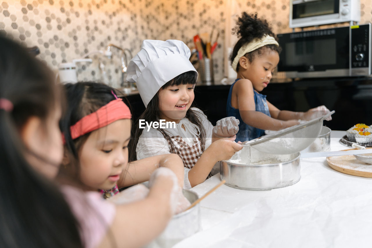 childhood, child, women, kitchen, togetherness, group of people, real people, indoors, girls, females, boys, lifestyles, domestic room, offspring, males, bonding, family, looking, home, innocence, preparing food, preparation, chef