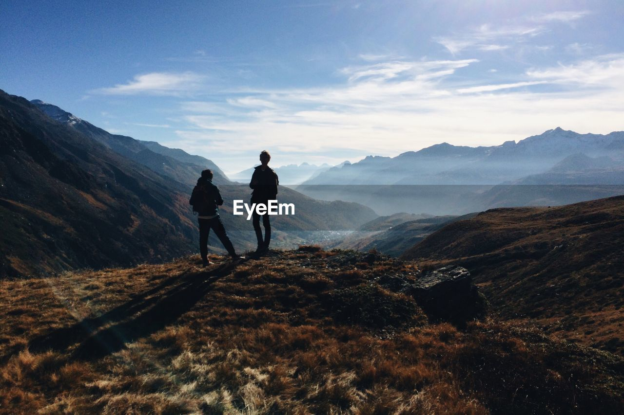 Rear view of people standing on mountain against sky
