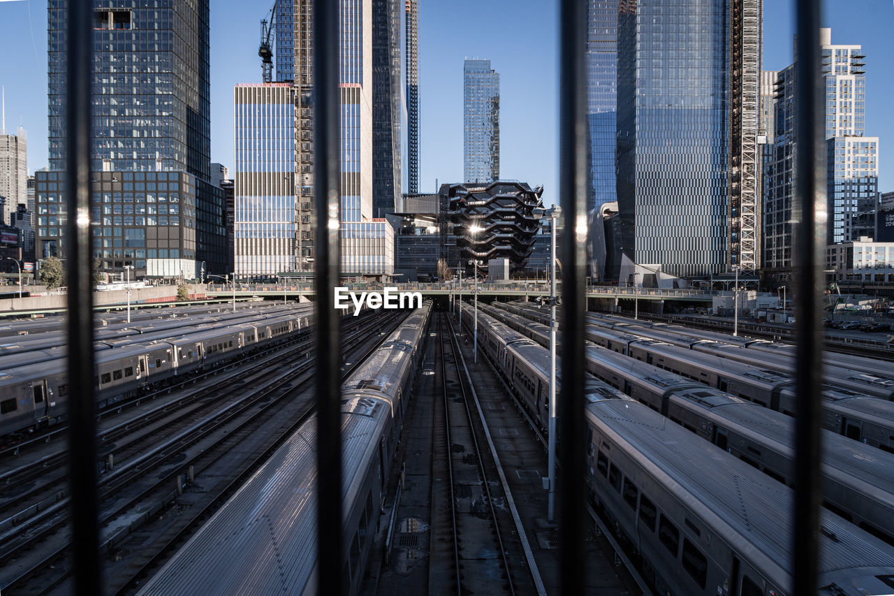 High angle view of trains against modern buildings in city seen through railing