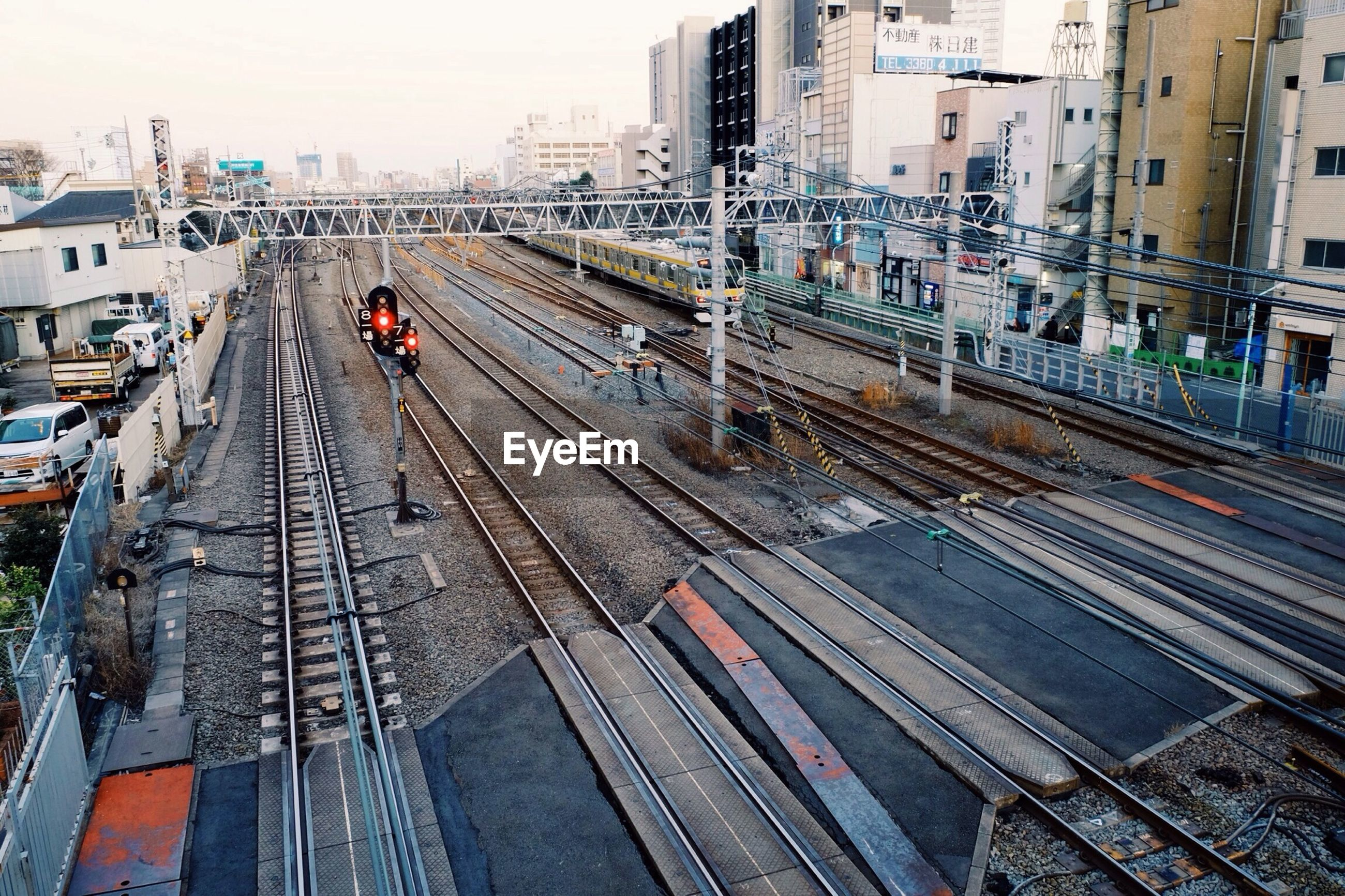 transportation, architecture, railroad track, built structure, building exterior, city, high angle view, public transportation, rail transportation, city life, mode of transport, travel, railroad station, railroad station platform, incidental people, the way forward, city street, traffic, on the move, diminishing perspective