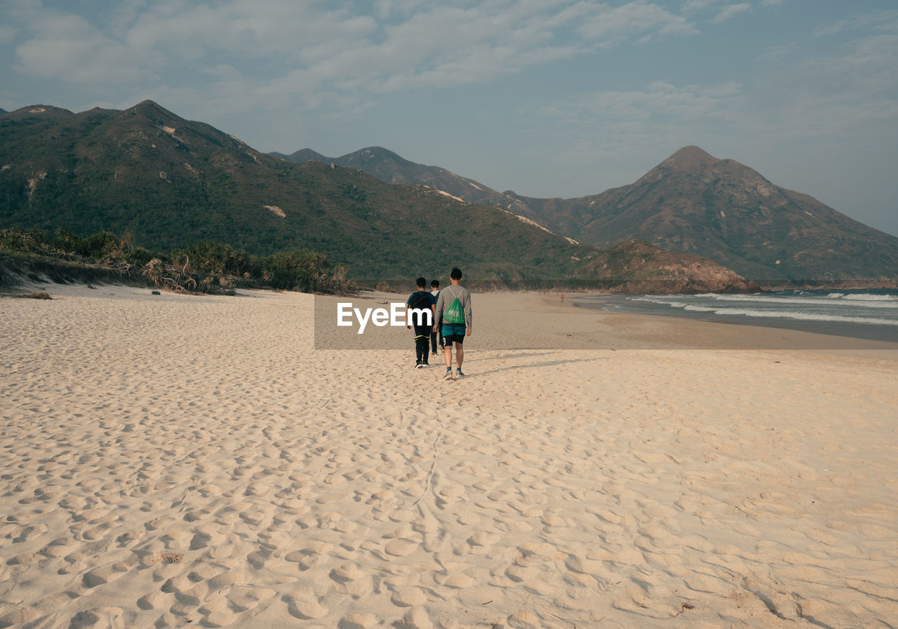 mountain, sky, land, beauty in nature, real people, scenics - nature, beach, men, sand, rear view, leisure activity, togetherness, nature, two people, non-urban scene, people, mountain range, cloud - sky, tranquility, full length, outdoors