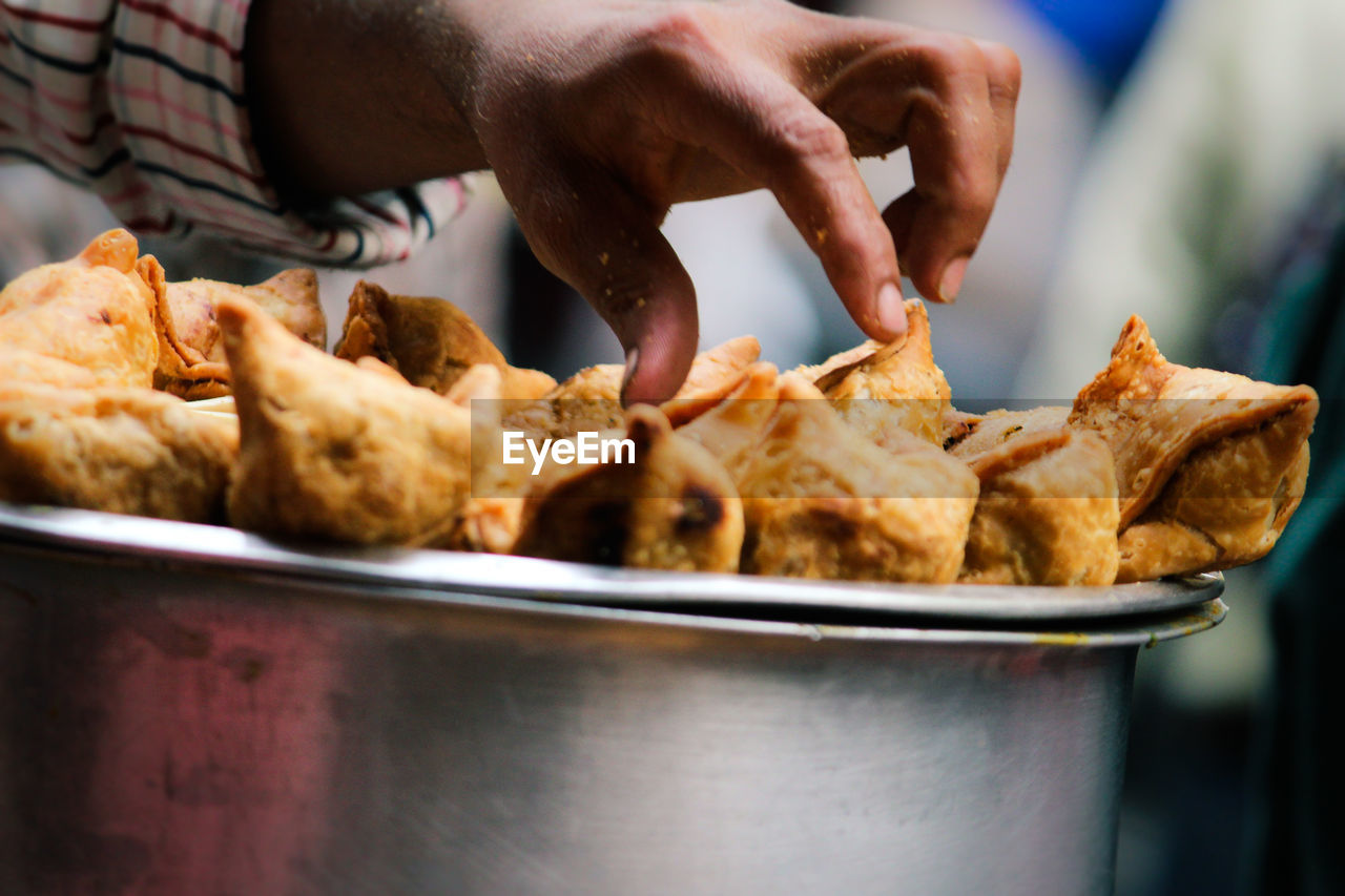 Cropped Hand Touching Samosas In Container