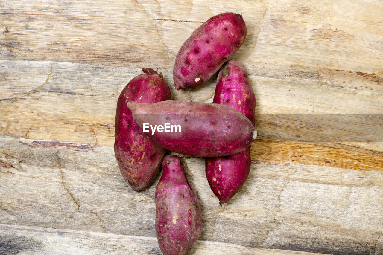food, food and drink, healthy eating, freshness, root vegetable, still life, wellbeing, no people, table, wood - material, raw food, high angle view, vegetable, directly above, sweet potato, pink color, indoors, close-up, group of objects, day, purple, common beet